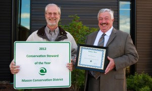 John Bolender (L), Mason Conservation District manager and Tom Farmer (R), PUD 3 Commission president show off stewardship sign and award certificate.