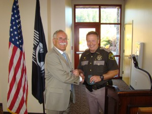 Sheriff Casey Salisbury presenting a coffee cup to Commissioner Peter Goldmark